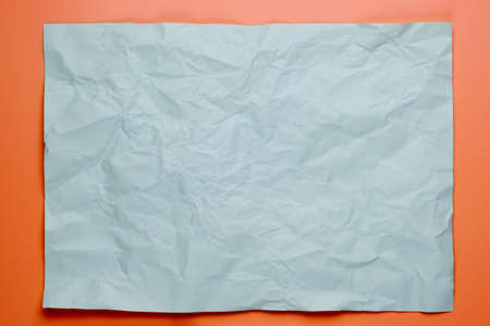 Close up of gray crumpled empty sheet of paper on pink background.