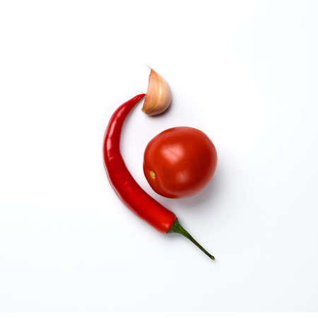 Red chili peppers, garlic and tomatoes isolated on white background.