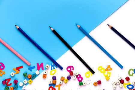 Many colorful drawing pencils and small letters on blue and white copy space background.