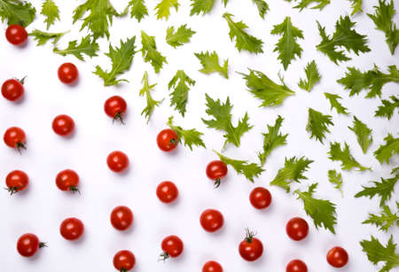 Red cherry tomatoes and green rucola salad leaves on white background.
