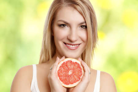 beautiful woman portrait with half of grapefruit photo