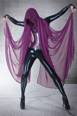 fetishism: Young woman in black latex catsuit with Cloth