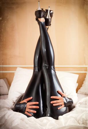 herrin: Frau in Latex im Bett Lizenzfreie Bilder