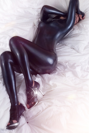 latex woman: sexy woman in latex in bed Stock Photo