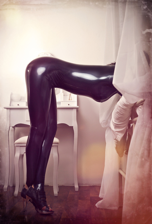 fetishism: sexy woman in latex in bedroom Stock Photo