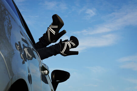 woman holds her feet from the car window