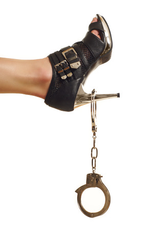 women s legs: shoes and handcuffs isolated on white background