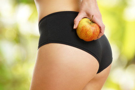 female butt: Beautiful female figure with apple Stock Photo