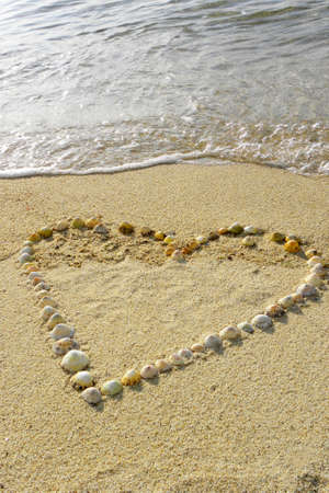 One heart in the sand with waves photo