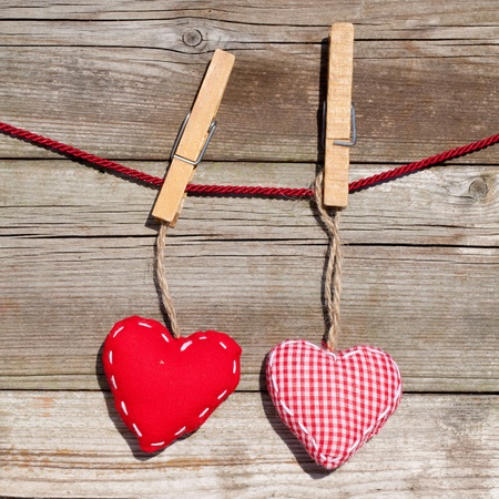 clothespin: hearts hanging on line against old wood
