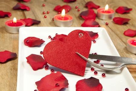 cena romantica: coperto per il giorno di San Valentino con petali Archivio Fotografico