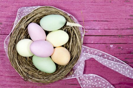 Easter eggs in nest on rustic wood photo