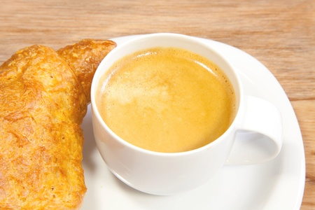 A cup of coffee and one croissant Stock Photo - 12534928