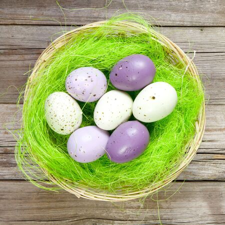easter nest with easter eggs on wooden background