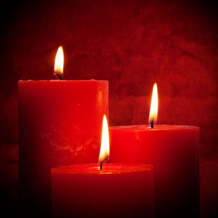 vela: Tres velas con el fondo rojo Foto de archivo