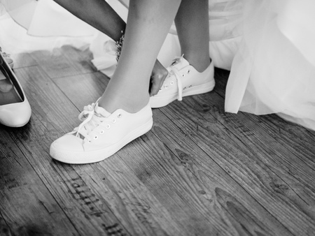 the bride takes off her bridal shoes and sneakers Stock Photo