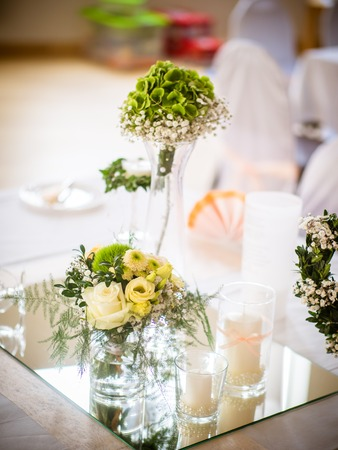 the small table decoration with white roses standing on a small mirror