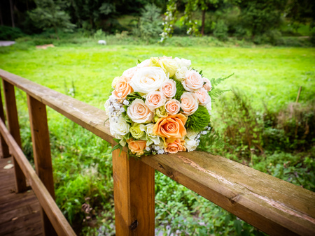 The bridal bouquet on the bridge with pink and orange roses Stock Photo