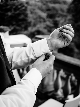 The groom closes his cufflinks, picture in black and white
