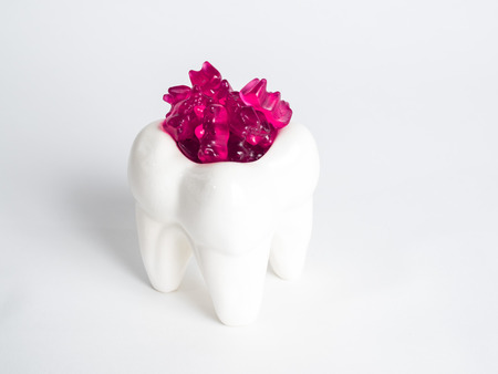 The porcelain tooth is filled with gummy bears against a white background Stock Photo