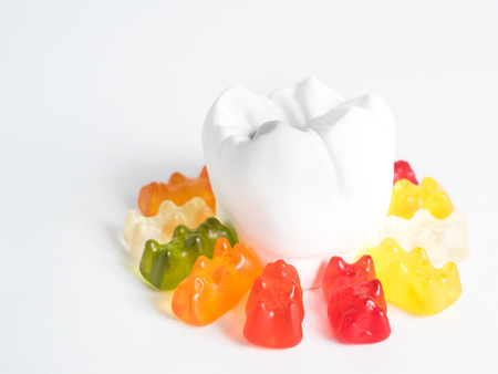 The gypsum tooth surrounded by gummy bears against a white background Stock Photo