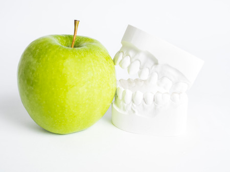 The plaster bit bites against a green apple against a white background isolated
