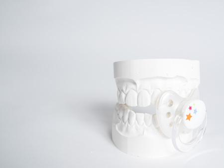 Minimizing the malocclusion caused by pacifiers, the gypsum tooth with the pacifier in front of the white background Stok Fotoğraf