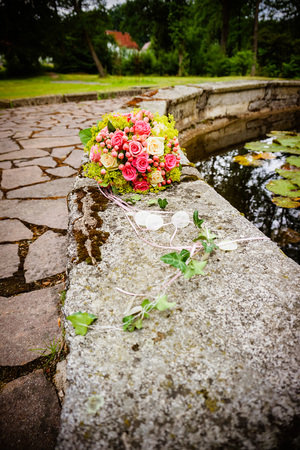 Romantic wedding fresh colorful bouquet in a daylight on the background of old baroque historical castle with park and fountain, wedding