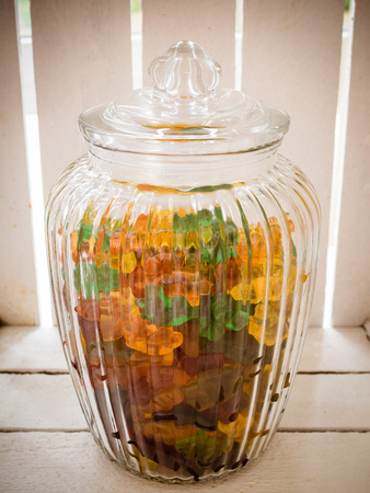 Assortment of jelly candy in a glass jar, with wood background, vintage candybar on the wedding Archivio Fotografico