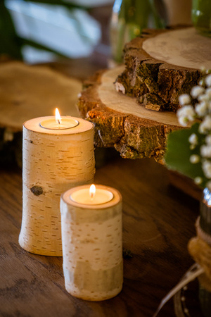 The candles in birch trunk, christmas and wedding decoration, wooden discs are in the background