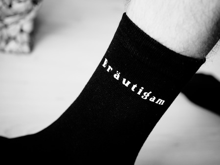 The legs of the stylish groom, cool sock with inscription groom Stock Photo
