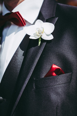 the groom in elegant black suit with orchid and red bow tie and red cloth on suit