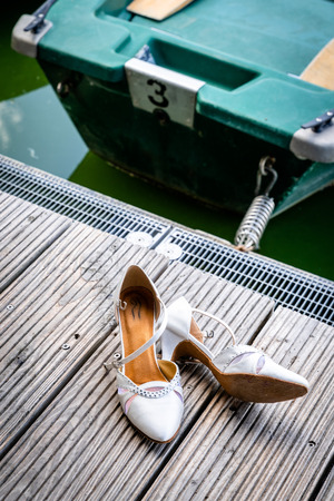 The shoes of the bride lie on the boat dock, escaped from the wedding, lovesession on the boat Archivio Fotografico