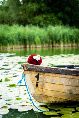Wedding bouquet on wooden boat, romantic picture on wedding day, bridal bouquet with red peonies and white orchids, in summer Archivio Fotografico