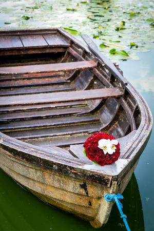 Wedding bouquet on wooden boat, romantic picture on wedding day, bridal bouquet with red peonies and white orchids, in summer Stock Photo