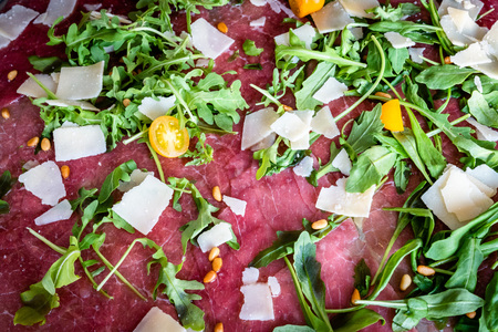 Beef carpaccio with arugula and parmesan cheese, taken from above