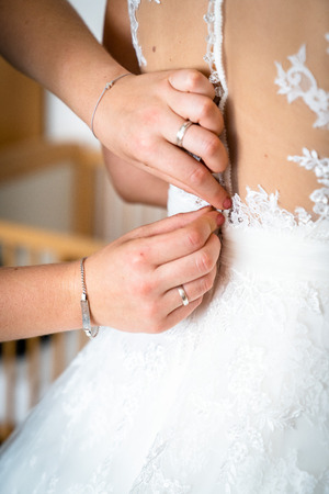 Bridesmaid helps the bride to dress, The dress is buttoned, 2 hands two hands close the bridal song on the back Stock Photo
