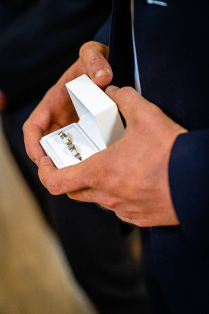 Handsome young man presenting something in a small box, wedding rings, a wedding ring, engagement ring, rings of gold
