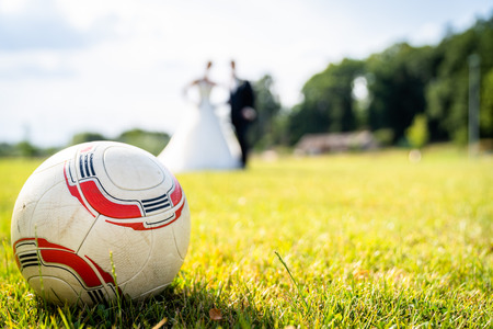 The newlyweds are standing on the soccer field with the ball in the foreground Archivio Fotografico