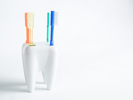 4 colored toothbrushes stand in glass, concept dental, The toothbrushes stand in a porcelain mug that looks like a tooth, picture for appointment cards