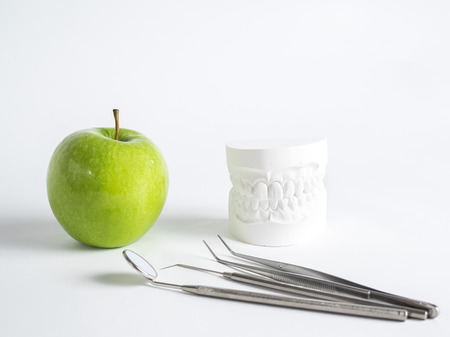 Green apple and dental tools isolated on white, with a gypsum denture Stockfoto
