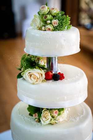 Wedding cake decorated with berries and flowers, with cream roses and red berries, blackcurrant, strawberry and sparkling deko balls
