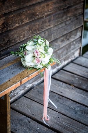 Bouquet for the bride of pink roses and white calla lilies, wood background