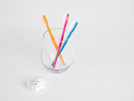 Three toothbrushes in a jar with baby pacifier on a white background healthy