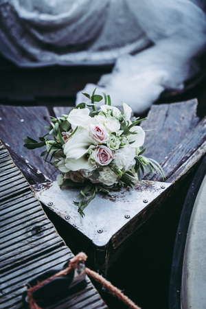 Bouquet for the bride of pink roses and white calla lilies, wood background, on the old wooden boat, in summer on the lake, cool Archivio Fotografico