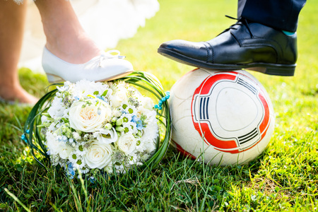 Bride and groom put their feet on the football, cool image and idea for photo shoot, wedding dress and suit can be seen