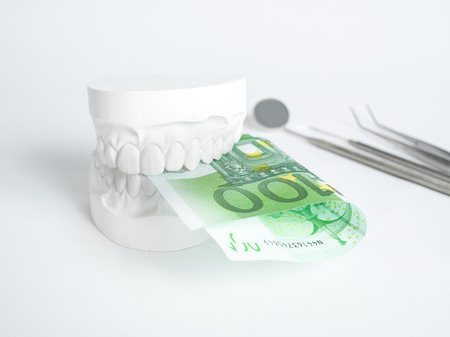 The denture with tooth money in euros on white backgrund Archivio Fotografico