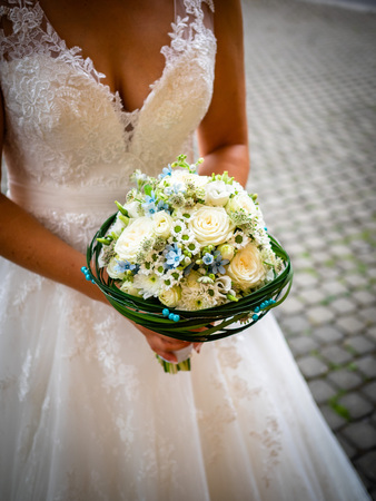 The bride holds the bouquet with white roses and little blue flowers, surrounded by green leaves and blue pearls, white lace dress, and daisies