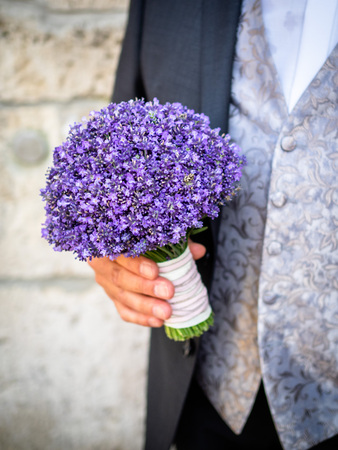 The groom holds the bridal bouquet, a bridal bouquet only from lilac lavender Archivio Fotografico