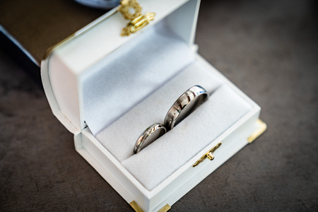 Wedding rings lie in box on the table near a bouquet silver Stock Photo